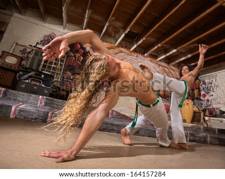 Young male capoeira partners performing kicks indoors - stock photo
