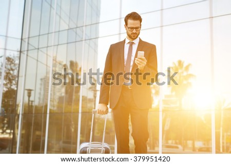 Young male CEO with suitcase reading text message on cell telephone while walking outdoors near building with city reflection, intelligent employer dials the number on smart phone before business trip - stock photo