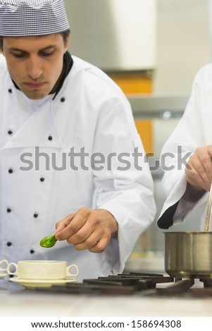 Young male chef garnishing a bowl soup with a basil leaf in kitchen - stock photo