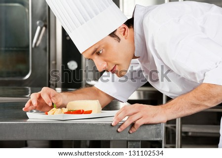 Young male chef garnishing dish in commercial kitchen - stock photo