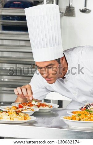 Young male chef garnishing pasta dishes at commercial kitchen counter - stock photo