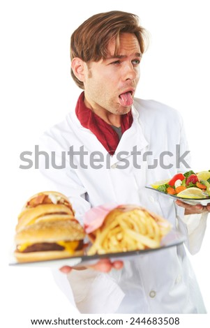 Young male chef sticking out tongue while holding burgers and French fries over white background - stock photo