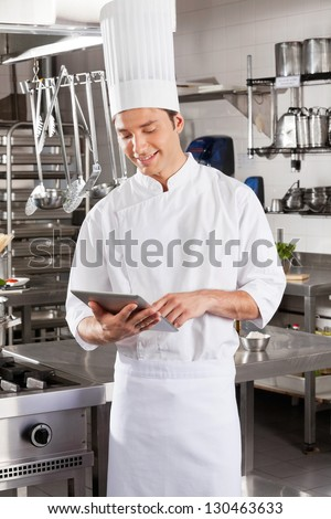 Young male chef using digital standing in restaurant kitchen