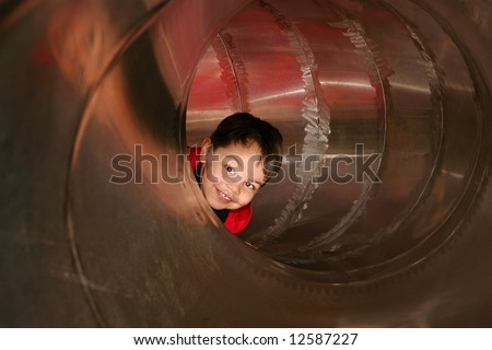 young male child playing sliding in a metal tube slide on a playground