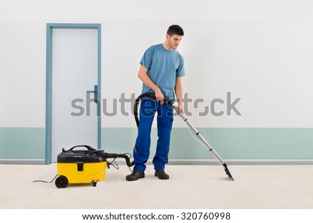 Young Male Cleaner In Uniform Vacuuming Floor - stock photo