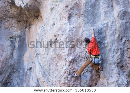 Young male climber hanging by a cliff. - stock photo