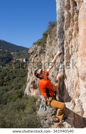 Young male climber hanging by a cliff.