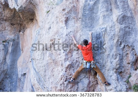 Young male climber hanging by a cliff