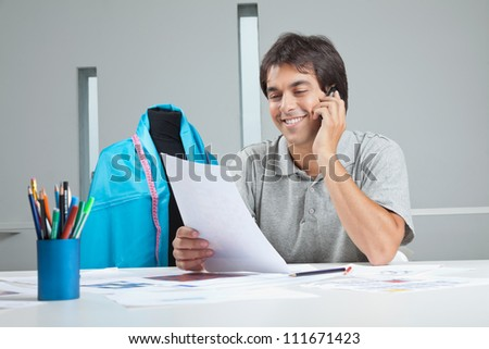 Young male clothing designer answering a phone call while holding paper