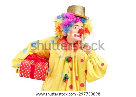 Young male clown holding a present wrapped in a red paper and holding a finger on his lips isolated on white background