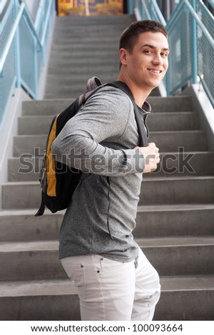 young male college student at school with backpack - stock photo