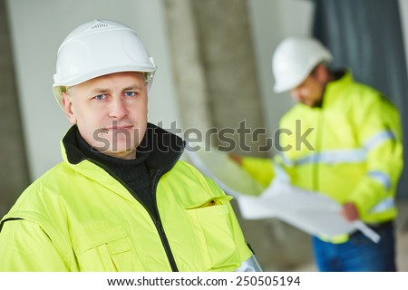 young male construction engeneer worker project manager at a indoors building site - stock photo