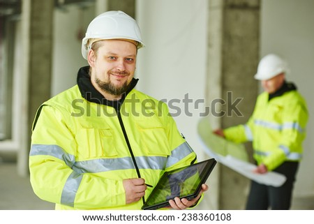 young male construction engeneer worker project manager with tablet pc at a indoors building site - stock photo