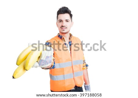 Young male constructor with gloves offering some bananas as healthy break concept isolated on white - stock photo