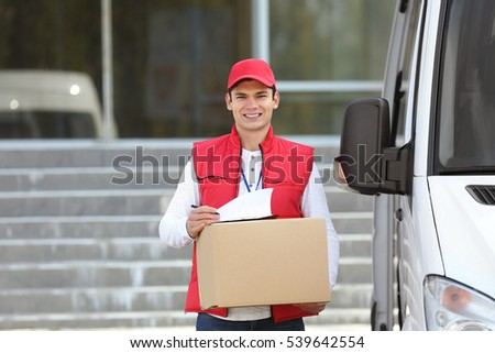 Young male courier with clipboard and parcel near delivery service van