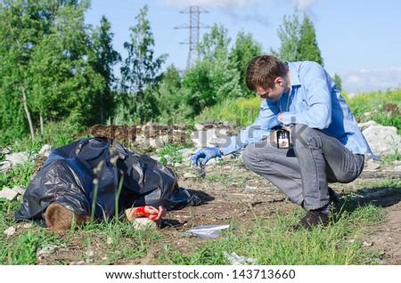 Young male criminalist inspecting crime scene - stock photo