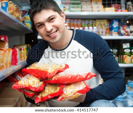 young male customer looking at assortment of pasta and smiling