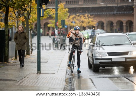 Young male cyclist in protective gear with backpack using walkie-talkie on street - stock photo