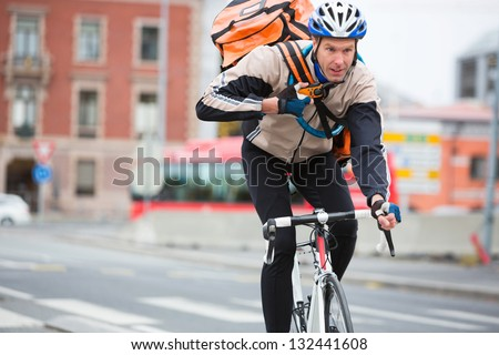 Young male cyclist with courier delivery bag riding bicycle on street - stock photo