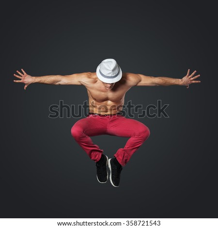 Young male dancer jumping isolated on gray background.