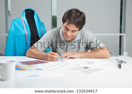 Young male designer drafting new designs on paper at workshop