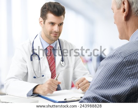 Young male doctor consulting with old patient at nursing home. - stock photo
