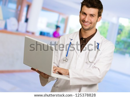 Young Male Doctor Holding Laptop, Indoor