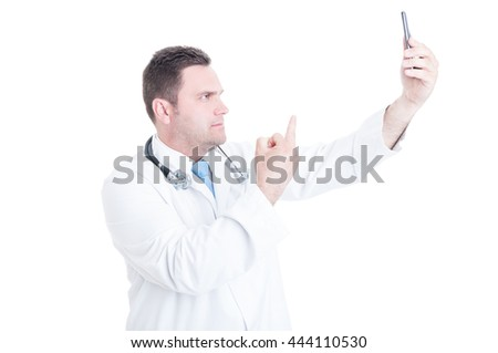 Young male doctor or medic taking selfie and showing middle finger gesture isolated on white background