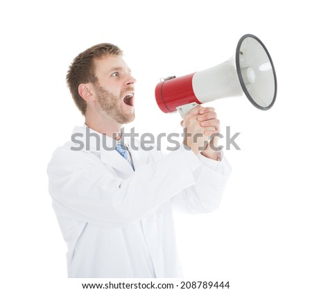 Young male doctor screaming into megaphone over white background - stock photo