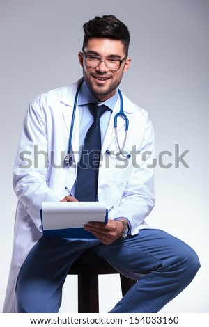 young male doctor sitting on a chair and writing something on his clipboard while smiling at the camera. on gray background - stock photo