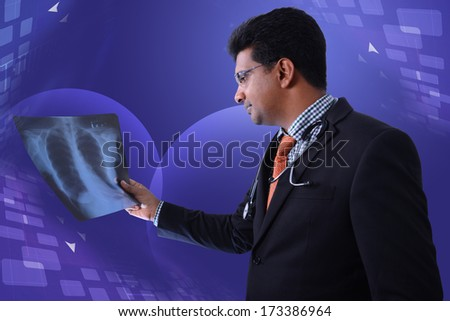 young male doctor watching patient x ray - stock photo