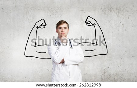Young male doctor with drawn strong hands behind his back - stock photo