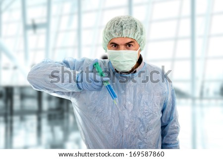 young male doctor with mask holding syringe - stock photo