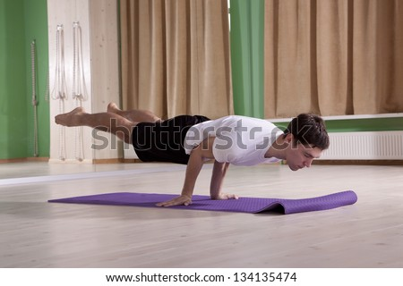young  male doing yoga - stock photo