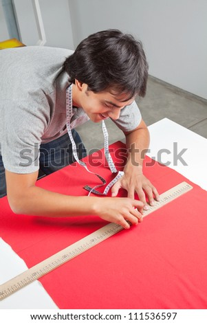 Young male dressmaker measuring a red fabric with ruler on table