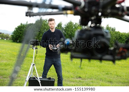 Young male engineer flying  UAV helicopter with remote control in park - stock photo