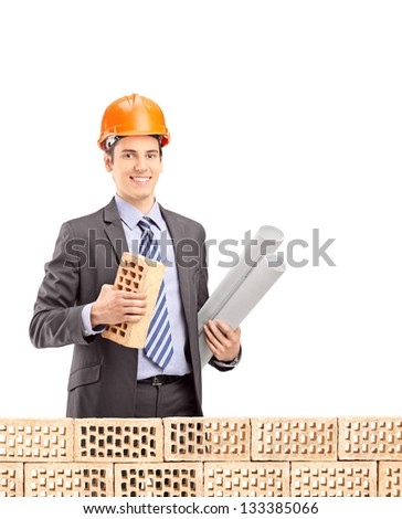Young male engineer holding a brick and a blueprint behind brick wall isolated on white background