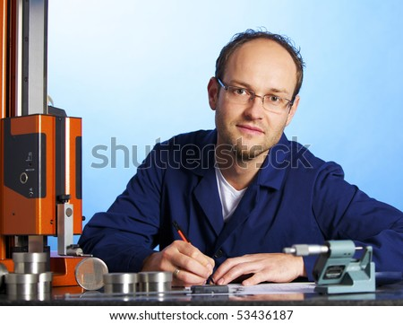 Young male engineer in blue overall recording precision measurement data of metal parts, isolated on blue background. - stock photo
