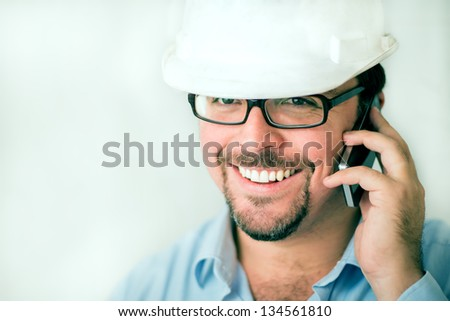 Young male engineer speaking on the phone - stock photo