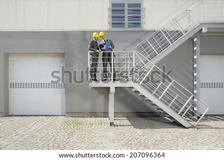 Young male engineers with clipboard discussing on stairway - stock photo