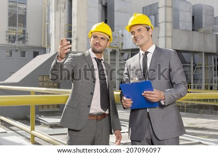 Young male engineers with clipboard discussing outside industry