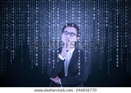 Young male entrepreneur in business suit, looking at binary code in futuristic computer screen - stock photo
