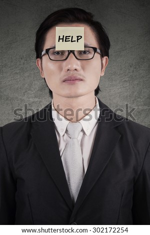 Young male entrepreneur needs help and attach a help text on his forehead - stock photo