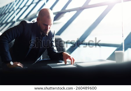 Young male executive examining paperwork in bight light office interior sitting next to the window, attractive business man read some documents before meeting, soft focus, filtered image - stock photo