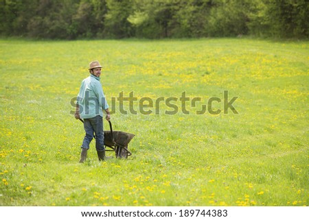 Young male farmer pushing wheelbarrow in the field
