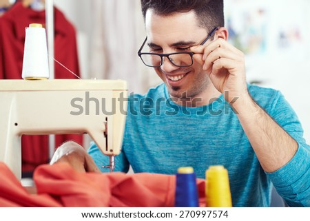 Young male fashion designer working on sewing machine - stock photo