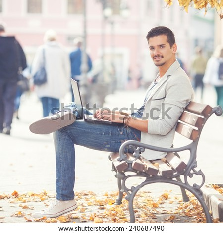 Young male fashion model with laptop sitting on the street bench - stock photo