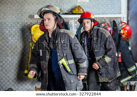Young male firefighters in uniforms walking at fire station - stock photo