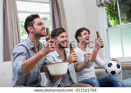 Young male friends enjoying beer while watching soccer match on TV - stock photo