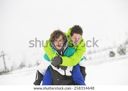 Young male friends enjoying piggyback ride in snow - stock photo